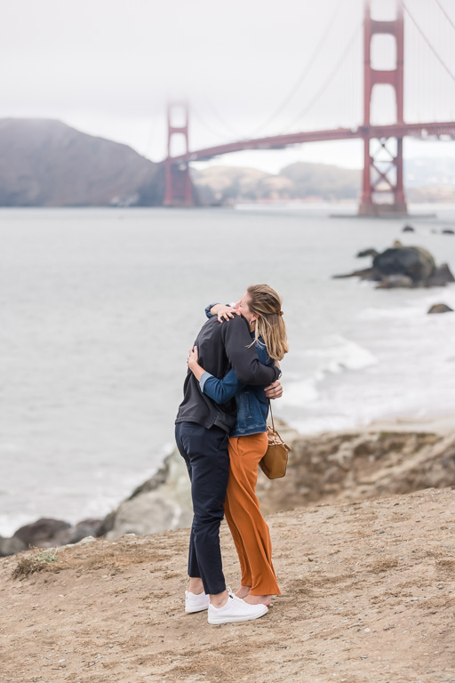 couple hugging in front of the Golden Gate Bridge