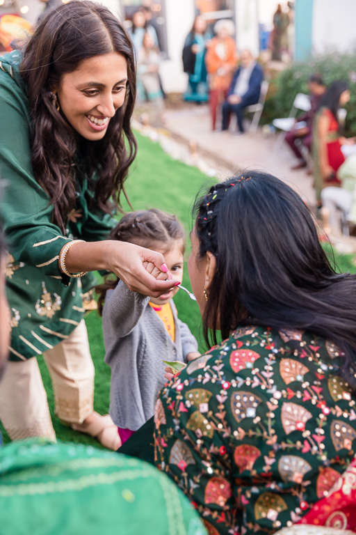 feeding the bride sweets during Indian mehndi ceremony