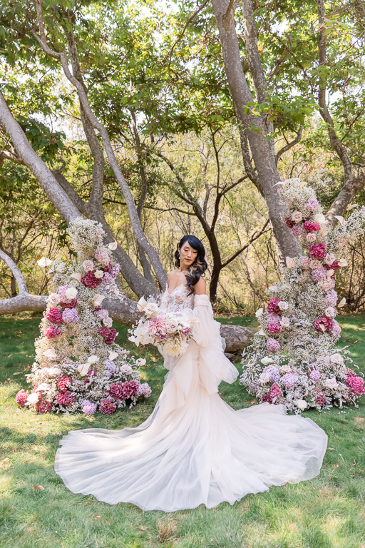 dreamy wedding bride in front of a lush floral arch
