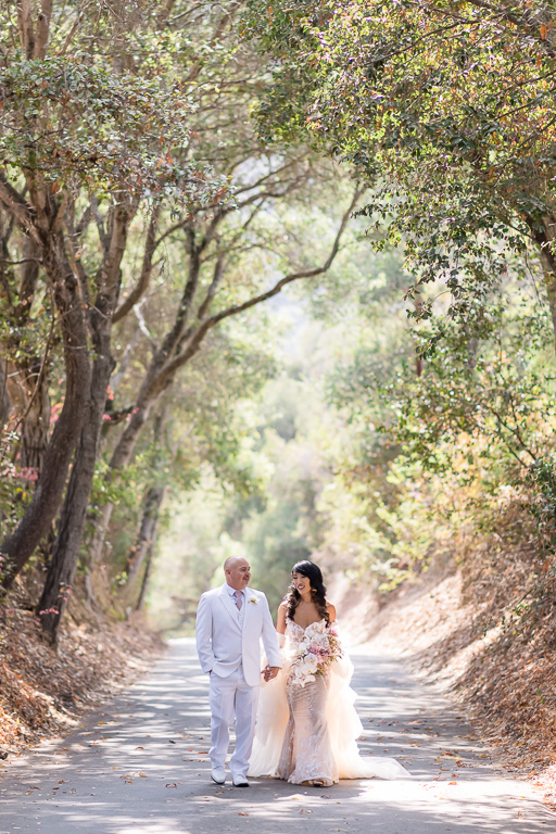 newlyweds walking in the tree tunnel
