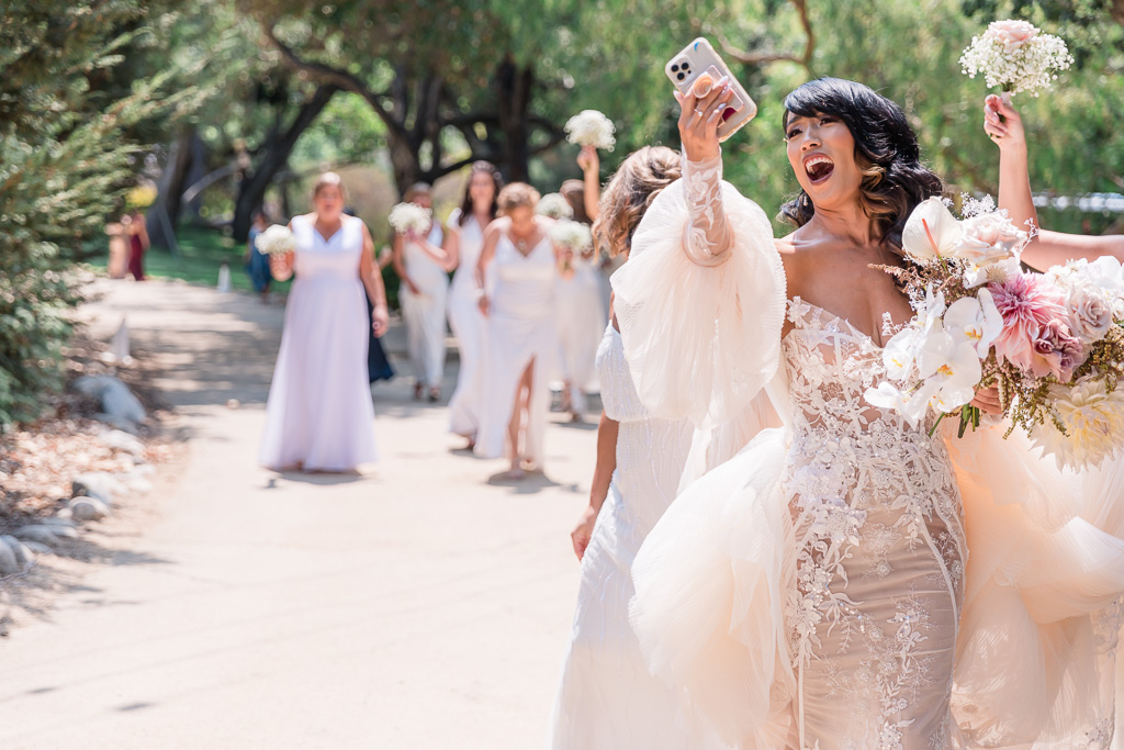 bride taking a selfie while walking with her gang