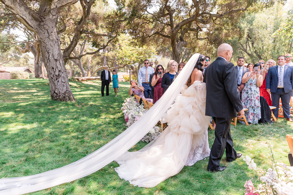bride walking down the aisle in her dramatic wedding gown and veil