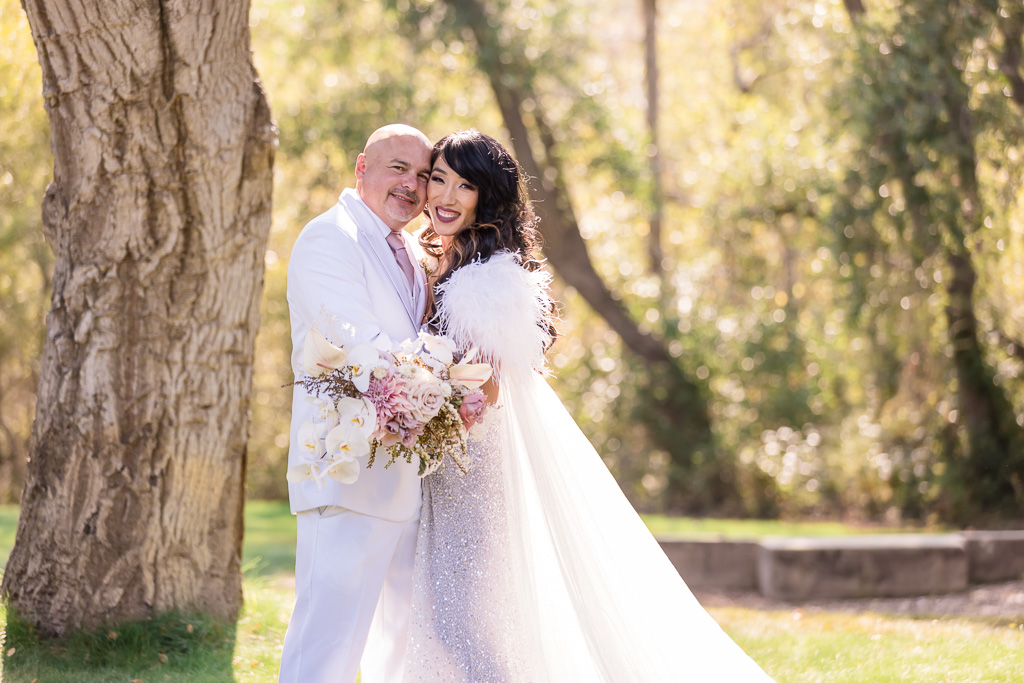 bride surprised groom with a sparkly reception gown and a feathery cape