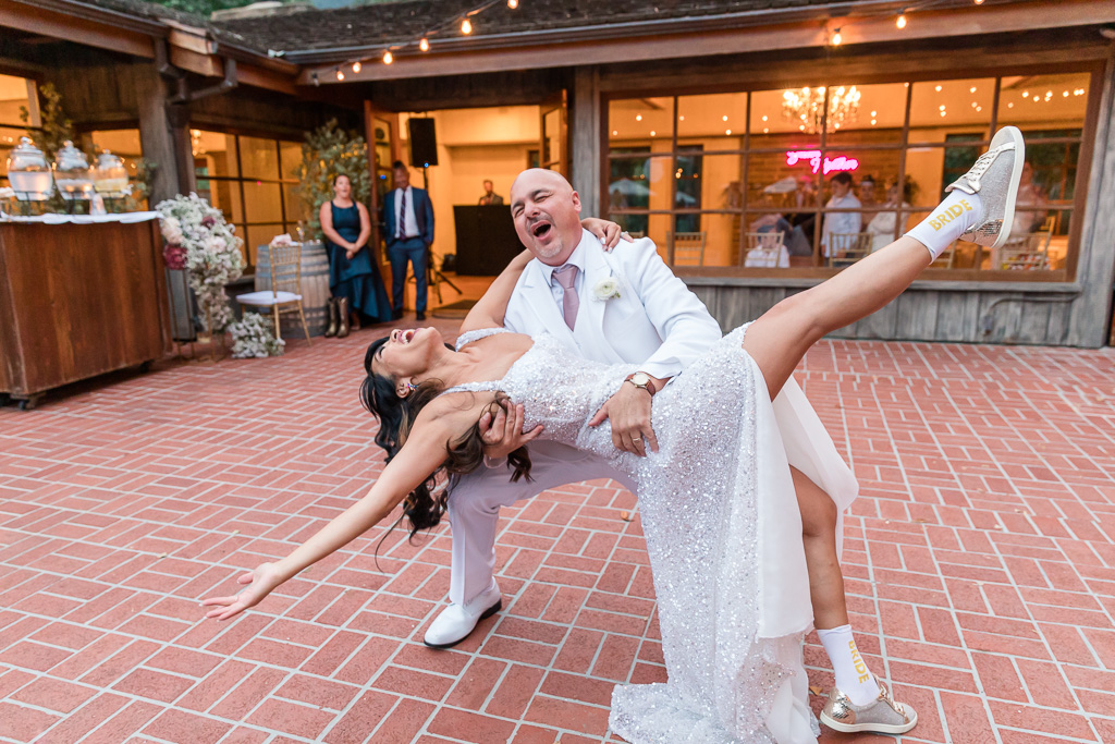 a dip at the end of their first dance in her bridal socks and sneakers